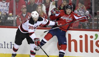 New Jersey Devils defenseman Seth Helgeson (39) battles along the boards against Washington Capitals right wing Tom Wilson (43) during the third period of an NHL hockey game, Saturday, Feb. 20, 2016, in Washington. The Capitals won 4-3. (AP Photo/Nick Wass)