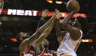 Miami Heat forward Justise Winslow (20) shoots over Washington Wizards forward Markieff Morris (5) and guard Ramon Sessions (7) during the second half of an NBA basketball game, Saturday, Feb. 20, 2016, in Miami. The Heat defeated the Wizards 114-94. (AP Photo/Lynne Sladky)