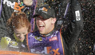 Denny Hamlin celebrates in Victory Lane after winning the NASCAR Daytona 500 Sprint Cup Series auto race at Daytona International Speedway in Daytona Beach, Fla., Sunday, Feb. 21, 2016. (AP Photo/Terry Renna)