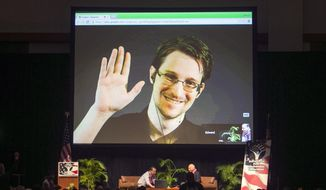 In this Feb. 14, 2015, file photo, Edward Snowden appears on a live video feed broadcast from Moscow at an event sponsored by ACLU Hawaii in Honolulu. (AP Photo/Marco Garcia, File)