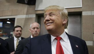 Republican presidential candidate Donald Trump smiles as he greets voters at a caucus site in this Tuesday, Feb. 23, 2016, file photo, in Las Vegas. (AP Photo/Jae C. Hong) ** FILE **