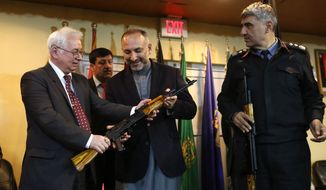 Russian Federation Ambassador, Alexander Mantytskiy, left, hands over an AK-47 to Afghan National Security Adviser Mohammad Hanif Atmar, center, as the symbol of his country's military donation to the Afghan government, at Kabul International Airport, Wednesday, Feb. 24, 2016. The Russian embassy in Kabul announced that the Russian government handed over 10,000 AK47s as a military donation to Afghan National Security Forces. (AP Photo/Rahmat Gul)