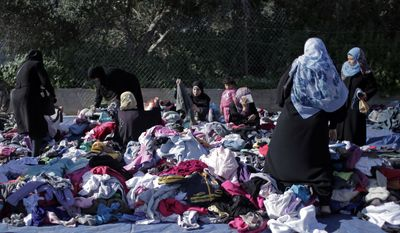 In this Monday, Feb. 15, 2016, file photo, Palestinian women sift through used clothing at the weekly flea market in Nusseirat refugee camp, central Gaza Strip. Demand for the garments has become a barometer for the economic situation in Gaza, where after nearly a decade of rule by the Hamas militant group, poverty and unemployment levels are higher than ever, and the market for used clothing, including those from Israel is buoyant. (AP Photo/Khalil Hamra)