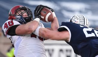 Harvard tight end Ben Braunecker, left, makes a touchdown reception against Yale linebacker Matthew Oplinger during an NCAA college football game, Saturday afternoon, Nov. 21, 2015, at the Yale Bowl in New Haven, Conn. (Catherine Avalone/New Haven Register via AP) MANDATORY CREDIT