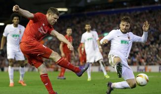 Liverpool's James Milner, left, fires in a shot on goal as FC Augsburg's Kostas Stafylidis attempts to block him during the Europa League, round of 32, second leg soccer match between Liverpool and FC Augsburg in Liverpool, England, Thursday Feb. 25, 2016. (AP Photo/Clint Hughes)