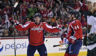 Washington Capitals defenseman Brooks Orpik (44) celebrates his goal with center Nicklas Backstrom (19), of Sweden, and left wing Alex Ovechkin (8), of Russia, during the second period of an NHL hockey game, as Minnesota Wild right wing Nino Niederreiter (22) skates by, Friday, Feb. 26, 2016, in Washington. (AP Photo/Nick Wass)