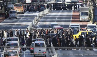 People cross crosswalks on a street in Tokyo, Friday, Feb. 26, 2016. The results of the 2015 census released Friday show the population dropped by 947,000 people in the last five years, the first decline since the count started in 1920. Japan's population stood at 127.1 million last fall, down 0.7 percent from 128.1 million in 2010. (AP Photo/Koji Sasahara)