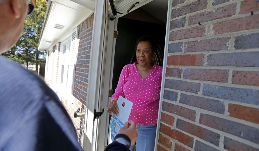 """Marq Anderson a canvasser for the campaign of Democratic presidential candidate Hillary Clinton, hands a flyer to Patricia Garvin as he canvasses a neighborhood for the """"Get Out The Vote"""" effort on voting day for the South Carolina Democratic primary in Columbia, S.C., Saturday, Feb. 27, 2016. (AP Photo/Gerald Herbert)"""