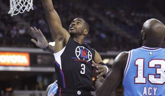 Los Angeles Clippers guard Chris Paul (3) drives to the basket past Sacramento Kings defender Quincy Acy (13) during the first half of an NBA basketball game in Sacramento, Calif., Friday, Feb. 26, 2016. (AP Photo/Steve Yeater)