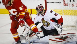 Ottawa Senators goalie Craig Anderson, right, kicks the puck away from Calgary Flames' Michael Frolik, from the Czech Republic, during the second period of an NHL hockey game Saturday, Feb. 27, 2016, in Calgary, Alberta. (Jeff McIntosh/The Canadian Press via AP)
