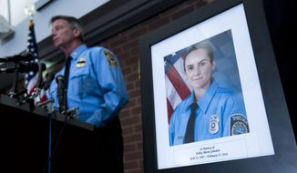 Prince William County Police Chief Stephan Hudson speaks during a news conference next to a picture of Officer Ashley Guindon at Western District Station in Manassas, Va., on Sunday. Saturday's killing of Guindon marks the most recent line of duty death this year. (Associated Press)