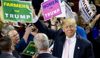 "Republican presidential candidate Donald Trump holds up a campaign sign that reads ""Farmers for Trump"" after speaking at a rally at Valdosta State University in Valdosta, Ga., Monday, Feb. 29, 2016. (AP Photo/Andrew Harnik)"