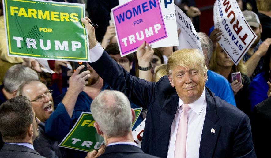 """Republican presidential candidate Donald Trump holds up a campaign sign that reads """"Farmers for Trump"""" after speaking at a rally at Valdosta State University in Valdosta, Ga., Monday, Feb. 29, 2016. (AP Photo/Andrew Harnik)"""