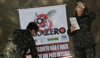 """FILE - In this Saturday, Feb. 13, 2016 file photo, army soldiers set up a sign that reads in Portuguese """"A mosquito is not stronger than an entire country"""" at the Central station in Rio de Janeiro, Brazil, as troops across Brazil try to tackle the Zika virus. Scientists may have the first evidence that Zika causes temporary paralysis, according to a new study of patients who developed the rare condition during an outbreak of the virus in Tahiti two years ago. The research was published online Monday, Feb. 29 in the journal, Lancet.  (AP Photo/Silvia Izquierdo, file)"""