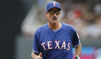 Texas Rangers pitching coach Mike Maddux returns to the dugout in a baseball game against the Minnesota Twins, Thursday, Aug. 13, 2015, in Minneapolis. (AP Photo/Jim Mone)