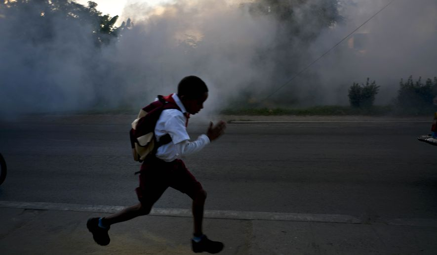 A student runs past fumigation fog, sprayed to kill Aedes Aegypti mosquitos, in Pinar del Rio, Cuba, Tuesday, March 1, 2016. Authorities are fumigating in an attempt to prevent the spread of Zika, Chikungunya and Dengue. (AP Photo/Ramon Espinosa)