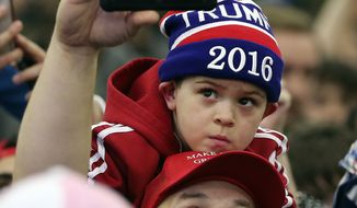 A man takes a selfie of himself and young boy as Republican presidential candidate Donald Trump signs autographs during a rally Tuesday, March 1, 2016, in Louisville, Ky. (AP Photo/John Bazemore)