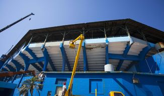 Workers use cranes to paint the Estadio Latinoamericano baseball arena in Havana, Cuba, Tuesday, March 1, 2016. On the same week as the visits by Obama and The Rolling Stones, the Tampa Bay Rays are expected to play the first Major League Baseball exhibition game in Cuba since 1999, part of an extraordinary string of events in a country that spent the Cold War isolated from the United States and its allies. (AP Photo/Desmond Boylan)