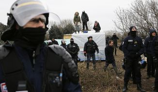 Police surrounds  activists standing on the roofs of dwellings in an attempt to prevent them from being dismantled in  a makeshift migrants  camp near Calais, France, Tuesday March 1, 2016. The slow tear-down of the encampment in Calais continued Tuesday, angering migrants who live there in squalid conditions in hopes of reaching a better life in Britain. (AP Photo/Jerome Delay)