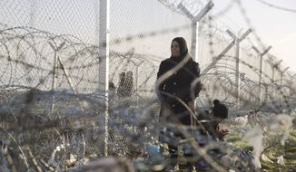A woman stands while another crouches down to check her mobile phone near the border crossing in front to a wire fence that separates the Greek side from the Macedonian one at the northern Greek border station of Idomeni, Wednesday, March 2, 2016. Greek police said up to 10,000 mostly Syrian and Iraqi refugees were stuck at the Idomeni border crossing in deteriorating conditions. (AP Photo/Petros Giannakouris)