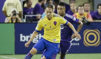 Colorado Rapids's Marcelo Sarvas, left, moves the ball past Orlando City's Cristian Higuita during the first half of an MLS soccer game, Wednesday, June 24, 2015, in Orlando, Fla. (AP Photo/John Raoux)
