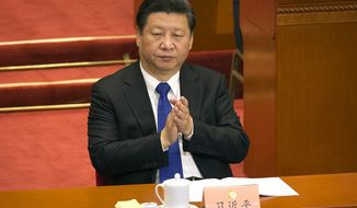 Chinese President Xi Jinping applauds during the opening session of the Chinese People's Political Consultative Conference in Beijing's Great Hall of the People, Thursday, March 3, 2016. Xi is set to further consolidate his all-encompassing hold on power at this week's annual session of the National People's Congress, China's rubber-stamp parliament. (AP Photo/Mark Schiefelbein)
