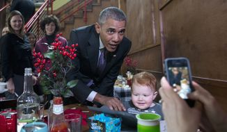 President Barack Obama poses for a photo with Finn Bode taken by his mother Courtney Bode at Engine Company No 3 in Milwaukee, Thursday, March 3, 2016. The president's trip to Milwaukee is to celebrate the city's victory in the Healthy Communities Challenge, a competition between 20 cities to increase the number of Americans with health insurance during the latest Health Insurance Marketplace open enrollment period. (AP Photo/Carolyn Kaster)