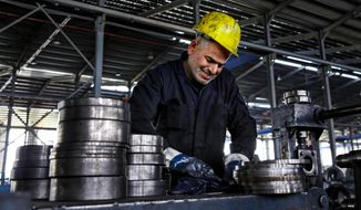A worker handles steel products at a factory for tubes and pipes in the Muwaqer Industrial Estate, in northern Jordan in this Thursday, Feb. 25, 2016, file photo. (AP Photo/Raad Adayleh)