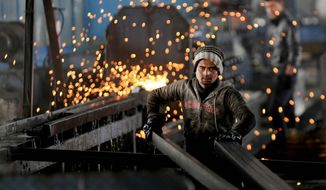 In this Thursday, Feb. 25, 2016 photo, a worker from India arranges steel tubes at a factory in the Muwaqer Industrial Estate, in northern Jordan. A new trade deal with Europe, a rush of foreign investment and ambitious public works are to put 200,000 Syrian refugees to work in Jordan in what the international community says is a precedent-setting new approach to the biggest displacement crisis in decades. (AP Photo/ Raad Adayleh)