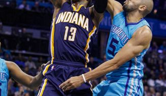 Charlotte Hornets guard Nicolas Batum, right, blocks the shot of Indiana Pacers forward Paul George during the first half of an NBA basketball game in Charlotte, N.C., Friday, March 4, 2016. (AP Photo/Nell Redmond)