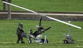 In this April 15, 2015, file photo, a member of a bomb squad checks a small helicopter after a man landed on the West Lawn of the Capitol in Washington. (AP Photo/Manuel Balce Ceneta, File)