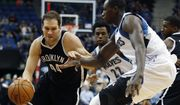 Brooklyn Nets guard Bojan Bogdanovic (44) drives the ball around Minnesota Timberwolves center Gorgui Dieng (5) in the first half of an NBA basketball game Saturday, March 5, 2016, in Minneapolis. (AP Photo/Stacy Bengs)