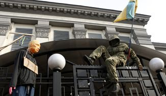 An activist in uniform climbs over the fence to the territory of the Russian embassy in Kiev, Ukraine, Sunday, March 6, 2016. About 2,000 people rallied on Independence Square in Kiev on Sunday to demand that Russia release Ukrainian pilot Nadezhda Savchenko, with hundreds then marching to the Russian Embassy to vent their anger. Savchenko was captured in June 2014 while fighting with a Ukrainian volunteer battalion against Russia-backed rebels in eastern Ukraine. She is now on trial in Russia, accused of acting as a spotter who called in coordinates for a mortar attack that killed two Russian journalists and several other civilians. (AP Photo/Sergei Chuzavkov)