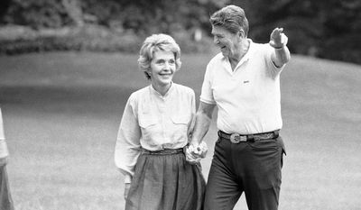 President Ronald Reagan and Mrs. Nancy Reagan greet reporters on the South Lawn of the White House shortly after their return from the presidential retreat at Camp David, Md., on July 22, 1984. The Reagan's spent the weekend at Camp David. (AP Photo/Tim Aubry)