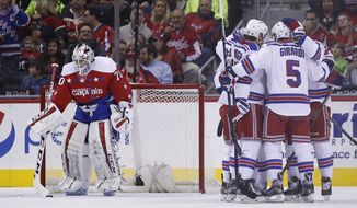 Teammates gather around New York Rangers right wing Jesper Fast (19), from Sweden, after his goal past Washington Capitals goalie Braden Holtby, left, in the first period of an NHL hockey game, Friday, March 4, 2016, in Washington. (AP Photo/Alex Brandon)