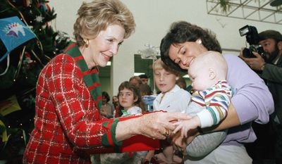 First Lady Nancy Reagan greets 5 month-old Kenneth Herbert of Capitol Heights, Md. while paying her annual Christmas visit to the Children's Hospital, National Medical Center on Tuesday, Dec. 17, 1985 in Washington. Mrs. Reagan gave the hospital a check for $25,000 donated by sponsors of the ?Christmas in Washington? television gala. Nurse Claudette Coddere holds Kenneth, a patient at the center. (AP Photo/Ira Schwarz)