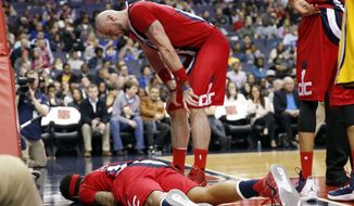 Washington Wizards center Marcin Gortat, center, from Poland, bends over to check on  guard Bradley Beal who was injured during the second half of an NBA basketball game against the Indiana Pacers, Saturday, March 5, 2016, in Washington. Beal left the game. The Pacers won 100-99. (AP Photo/Alex Brandon)