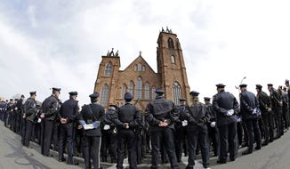 Police stand outside Sacred Heart Church for the funeral of Prince William County, Va., Police Officer Ashley Guindon, Monday, March 7, 2016, in Springfield, Mass. Guindon, 28, a Springfield native, was killed during her first shift on the job Feb. 27 while responding to a domestic dispute in Woodbridge, Va. (AP Photo/Elise Amendola)
