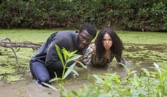 "This image released by WGN shows Aldis Hodge, left, and Jurnee Smollett-Bell in a scene from ""Underground,"" a new drama series premiering on WGN America on Wednesday at 10 p.m. EDT. (Skip Bolen/Sony Pictures Television via AP)"