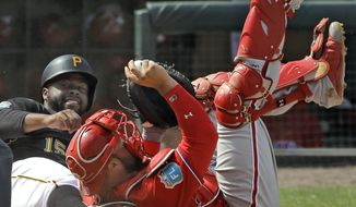 Philadelphia Phillies catcher Cameron Rupp, right, hangs onto the ball after tagging out Pittsburgh Pirates' Jason Rogers, left, at home plate during the fifth inning of a spring training baseball game Monday, March 7, 2016, in Tampa, Fla. Rogers was trying to score on a hit by Alen Hanson. (AP Photo/Chris O'Meara)