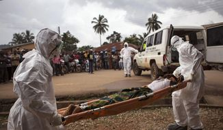 In this Sept. 24, 2014, file photo, health care workers load a man suspected of suffering from the Ebola virus onto an ambulance in Kenema, Sierra Leone. (AP Photo/Tanya Bindra, File)
