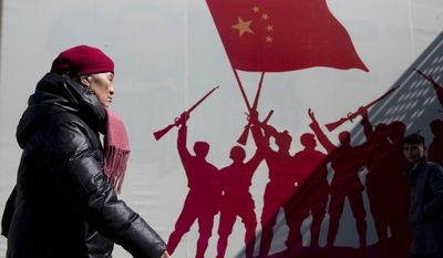 A woman walks near a patriotic mural depicting Chinese soldiers celebrating, in Beijing Tuesday, March 8, 2016. Chinese Foreign Minister Wang Yi took a hard line Tuesday on the country's claims to virtually all the South China Sea, saying Beijing won't permit other nations to infringe on what it considers its sovereign rights in the strategically vital area. (AP Photo/Ng Han Guan)