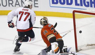 Washington Capitals right wing T.J. Oshie (77) scores against Anaheim Ducks goalie John Gibson (36) during an overtime shootout in an NHL hockey game in Anaheim, Calif., Monday, March 7, 2016. The Capitals won 2-1. (AP Photo/Christine Cotter)