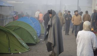 A migrant covered in a blanket walks at the northern Greek border station of Idomeni, Tuesday, March 8, 2016. Greek police officials say Macedonian authorities have imposed further restrictions on refugees trying to cross the border, saying only those from cities they consider to be at war can enter. (AP Photo/Visar Kryeziu)