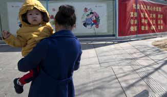 A woman carries a child near government propaganda promoting filial piety on the streets of Beijing, China, Tuesday, March 8, 2016. China has no plans to allow couples to have as many kids as they want after changing the rules to allow all couples to have two children rather than one, a health official said Tuesday.(AP Photo/Ng Han Guan)