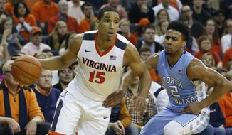 In this photo taken, Saturday Feb. 27, 2016, Virginia guard Malcolm Brogdon (15) drives to the basket past North Carolina guard Joel Berry II (2) during the second half of an NCAA college basketball game in Charlottesville, Va. Brogdon has been at the heart of winning games, leading Virginia in scoring for three consecutive years. (AP Photo/Steve Helber)