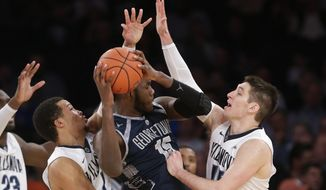 Villanova's Ryan Arcidiacono, right, and Jalen Brunson, left, defend Georgetown's Jessie Govan (15) during the first half of an NCAA college basketball game during the Big East men's tournament Thursday, March 10, 2016, in New York. Villanova won 81-67. (AP Photo/Frank Franklin II) **FILE**