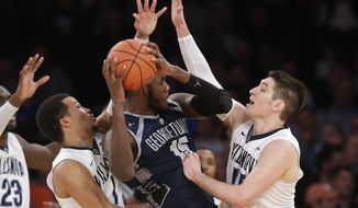 Villanova's Ryan Arcidiacono, right, and Jalen Brunson, left, defend Georgetown's Jessie Govan (15) during the first half of an NCAA college basketball game during the Big East men's tournament Thursday, March 10, 2016, in New York. Villanova won 81-67. (AP Photo/Frank Franklin II)