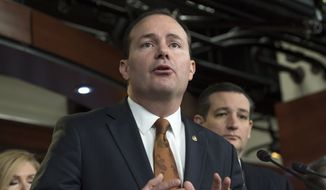 Sen. Mike Lee, Utah Republican, accompanied by Sen. Ted Cruz, Texas Republican and 2016 presidential candidate, speaks during a news conference on Capitol Hill in Washington on Feb. 12, 2015. (Associated Press) **FILE**