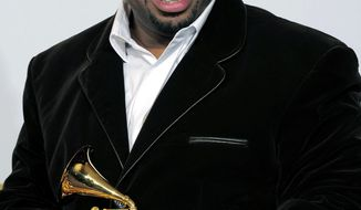 """FILE - In this Feb. 12, 2012, file photo, Christian McBride, of the Christian McBride Big Band, poses backstage with the award for best large jazz ensemble for """"The Good Feeling"""" at the 54th annual Grammy Awards in Los Angeles. The Newport Festivals Foundation announced Thursday, March 10, 2016, that McBride has been named artistic director of the Newport Jazz Festival. McBride will work side-by-side with George Wein at the Rhode Island festival in 2016, and take the reins for the 2017 festival. (AP Photo/Mark J. Terrill, File)"""